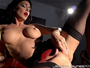 kinky black-haired Jessica Jaymes thumbs her tasty gash pie in her office