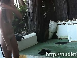 Spy web cam shot of a torrid nudist babe tanning on the beach